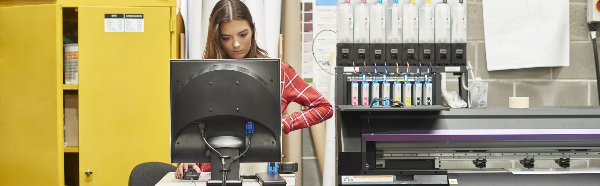 A young woman is working on a digital printing machine.